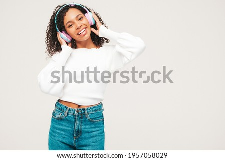 Beautiful black woman with afro curls hairstyle.Smiling model in sweater and jeans.Sexy carefree female listening music in wireless headphones.Posing in studio on white background