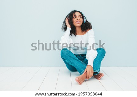 Beautiful black woman with afro curls hairstyle.Smiling model in sweater and jeans.Sexy carefree female listening music in wireless headphones.Sitting in studio near light blue wall
