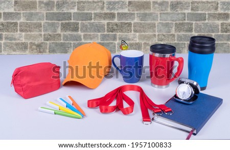 Composition of different promo products with rich colors -Thermo mugs, Lanyards Neck Strap, pens, mug, silver table office clock, zipped coin purse fabric, notebook,cap On desk grey and background gre Royalty-Free Stock Photo #1957100833