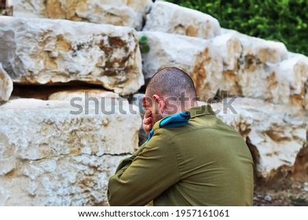 Israeli soldier crying and mourning for the fallen soldiers. Concept: Israeli soldiers, Israel Memorial Day - Yom HaZikaron Royalty-Free Stock Photo #1957161061