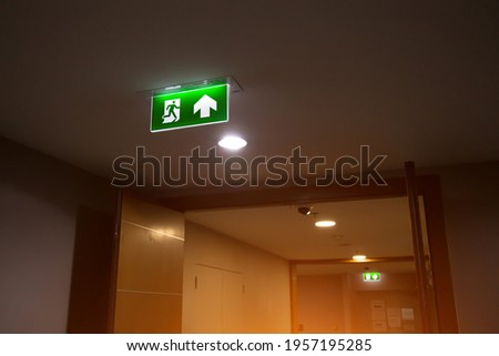 Close up the green emergency fire exit sign or fire escape with the doorway or door exit in the building concepts for evacuation in the event of a fire.