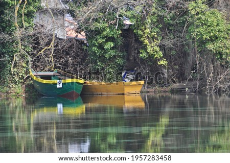 A photograph of two small stationary fishermen boats on Ohrid spring close to Lake Ohrid in North Macedonia on the grounds of St Naum Monastery on a sunny day.