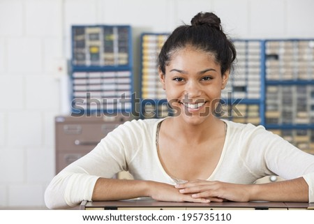 Portrait of female engineering student smiling at lab bench in electrical engineering laboratory #195735110