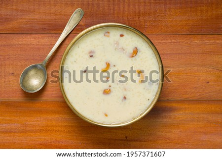 Indian sweet dish Rice Palada  Payasam or Kheer_ main sweet dish made during special occassions_using rice pastha bits,milk,sugar and dry nuts arranged in a brass vessel with wooden background