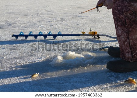 A fisherman in warm winter clothes catches fish on a spinning rod in a hole in the ice of the river in winter.