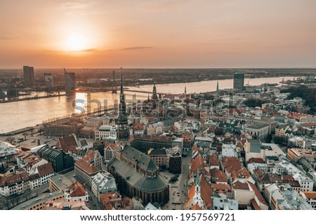 RIga rooftop view panorama at sunset with urban architectures and Daugava River. View of the old town Royalty-Free Stock Photo #1957569721