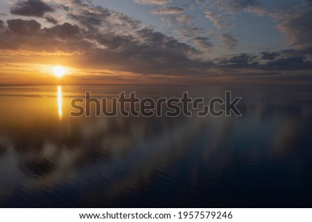 Early morning sunrise over the sea . Some clouds. Royalty-Free Stock Photo #1957579246