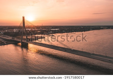 Bridge over river at sunset Royalty-Free Stock Photo #1957580017