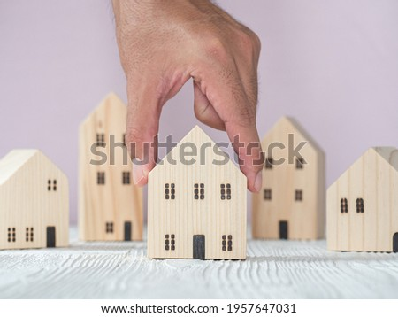 Hand choosing wooden house model from row of model on white wood table, selective focus. Planning to buy property. Choose what's the best. Mortgage and real estate property investment.