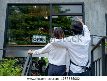 Back of couple coffee makers or coffee shop staffs that man point to the building and talk to woman. Concept of good teamwork support small business system.