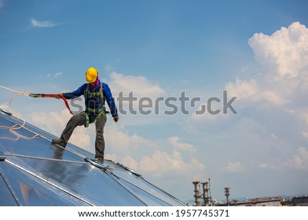 Male workers rope access height safety connecting with a knot safety harness, clipping into roof fall arrest and fall restraint anchor point systems ready to ascending, construction site oil tank dome Royalty-Free Stock Photo #1957745371