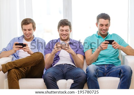 friendship, technology and home concept - smiling male friends with smartphones at home #195780725