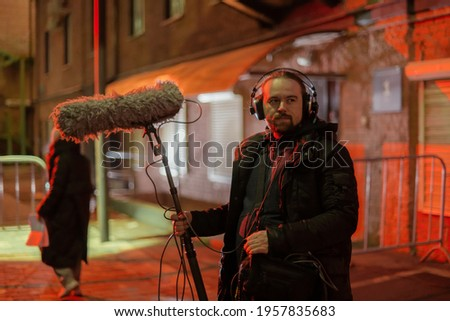 Sound engineer with a microphone on the set. A professional sound engineer at work on the filming of a movie, commercial or TV series. Filming process indoors, studio