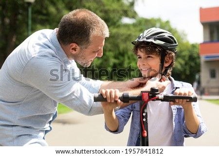 Safety Concept. Close up portrait of smiling adult father putting protection helmet on little boy at park, teaching his brave son to ride electric motorized scooter. Ourdoor Weekend Activity Royalty-Free Stock Photo #1957841812