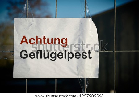 Sign at the entrance of a farm in Germany with the inscription Attention avian influenza (Achtung Geflügelpest)                                Royalty-Free Stock Photo #1957905568