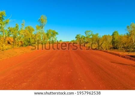 Scenic Outback road in the Northern Territory, Central Australia in in the Red Center. Red sand dirt road between Alice Springs and Finke Gorge National Park. Royalty-Free Stock Photo #1957962538