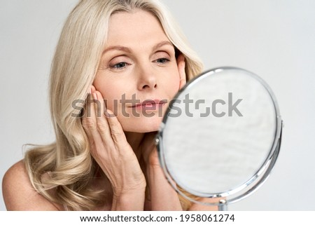 Closeup portrait of gorgeous happy middle age woman looking at mirror touching her skin enjoying treatment for dry skin. Advertising of antiaging beauty skin care products. Royalty-Free Stock Photo #1958061274