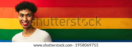 Portrait of a gay man wearing make up against pride flag. Gender fluid male with red lip stick and earring looking away and smiling. Banner with copy space.