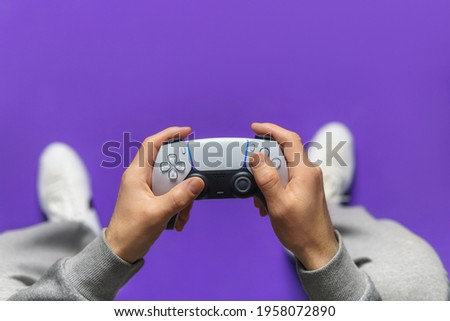 Hand hold new joystick. Gamer play game with gamepad controller. Gaming man holding simulator joypad. Person with keypad joystic in arms. happy to win. clenched fist. Gaming concept. Royalty-Free Stock Photo #1958072890