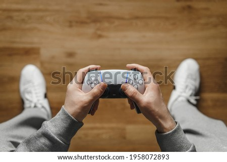 Hand hold new joystick. Gamer play game with gamepad controller. Gaming man holding simulator joypad. Person with keypad joystic in arms. happy to win. clenched fist. Gaming concept. Royalty-Free Stock Photo #1958072893