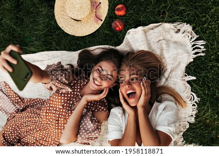 Emotional young tanned girls in stylish dresses take selfie and smile outdoors. Brunette woman holds phone. Charming ladies have picnic in park.