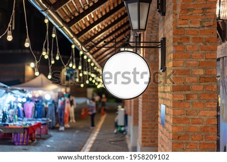 The Circle white Lightbox has hung on the wall in front of the brick pole in a Tungsten ambient environment vintage shopping community mall.