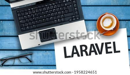 Laravel PHP Framework programming language. Word Laravel on paper and laptop Royalty-Free Stock Photo #1958224651