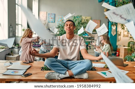 Keep calm and no stress! Young African-American man is sitting in lotus position while his colleagues are arguing nearby. Multiracial people working together in modern office. Royalty-Free Stock Photo #1958384992