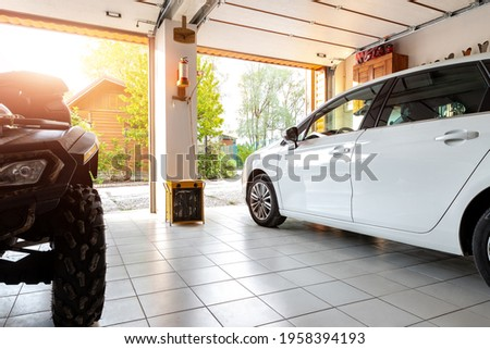 Home suburban countryside modern car and ATV double garage interior with wooden shelf, tools and equipment stuff storage warehouse indoors against sun light. Vehicle parked house parking background Royalty-Free Stock Photo #1958394193