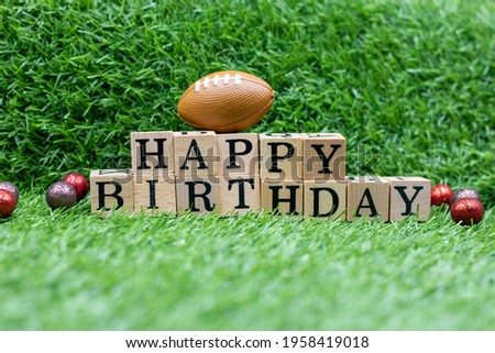 American football with word happy Birthday are on green grass