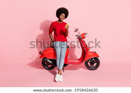 Full size photo of dark skin person sitting on moped look phone typing blog post isolated on pink color background