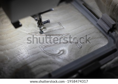 Embroidery design, alphabet M monogram. Machine Embroidery on a cotton towel with brown thread. Close up.