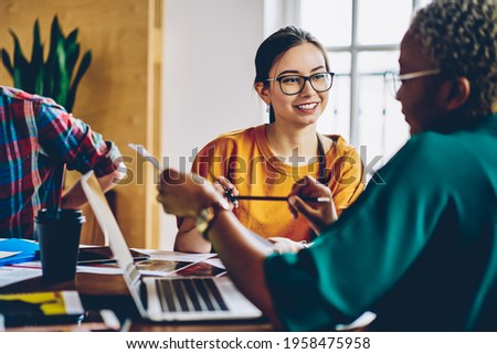 Carefree Caucasian employee in optical spectacles for provide eyes correction talking with dark skinned colleague discussing paperwork during collaborative briefing at desktop, business concept Royalty-Free Stock Photo #1958475958