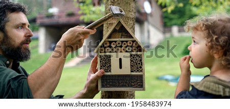 Small girl with father holding bug and insect hotel in garden, sustainable lifestyle. Royalty-Free Stock Photo #1958483974