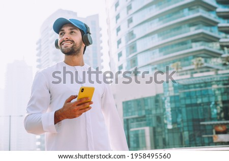 Beautiful middle eastern man wearing kandora traditional outfit in Dubai. Portraits in the emirates Royalty-Free Stock Photo #1958495560