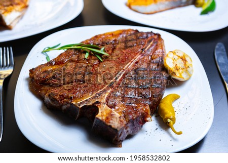 Delicious t-bone steak cooked on grill for dinner.Gourmet beefsteak served for dinner on white plate in American meat restaurant.Download royalty free curated images collection with foods for design