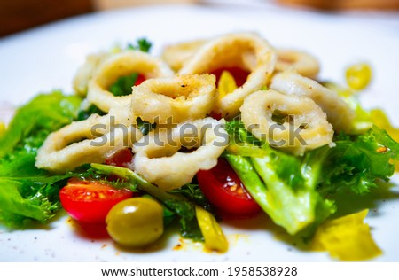 Delicious sea food.Squid salad with octopus rings,fresh green leaves, olives and tomatoes served on white plate in Asia seafood restaurant.Download royalty free curated images collection with foods