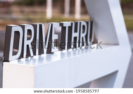 Drive thru sign with a big arrow pointing somewhere outside frame