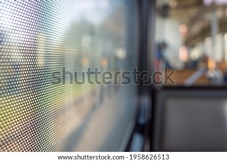 Selective focus, close-up view at One Way Vision sticker film with dot pattern on glass of Train's window and blurry background of train's passenger train and bokeh. Royalty-Free Stock Photo #1958626513