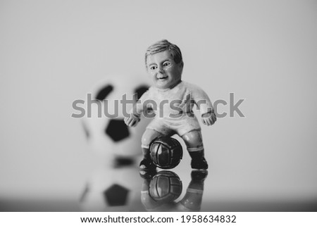 Football game concept, close-up of a model footballer from the 70s with a ball with the classic pentagons behind it, black and white image.