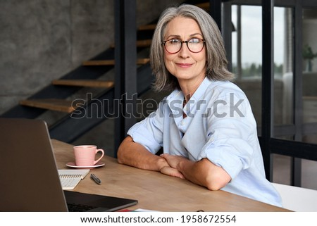 Portrait of smiling Middle age 60s aged business woman working at home office with laptop, headshot of happy woman worker or ceo posing for corporate photoshoot, looking at camera. Royalty-Free Stock Photo #1958672554
