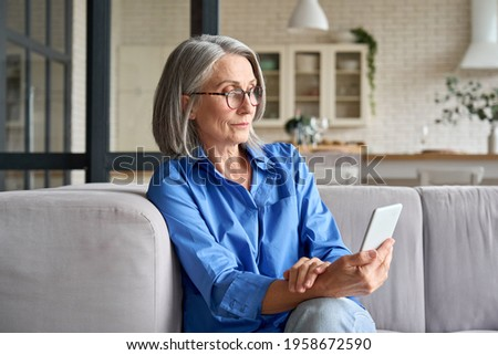 Serious mature middle age senior woman at home on couch holding mobile cellphone, reading news or watching online learning class having video call using mobile application. Royalty-Free Stock Photo #1958672590