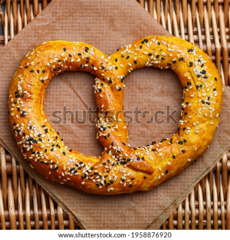 Freshly baked homemade Pretzel with black and white sesame seeds. German (Bavarian) beer appetizer. Traditional savory pastries. Selective focus, square picture