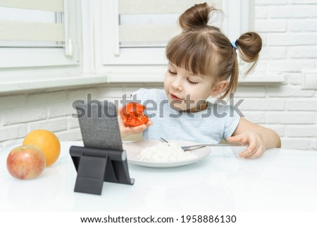 kid girl eating food and watching cartoons on a smartphone. Organic food and vegetables on a plate. A way to feed children