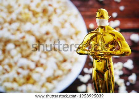 Hollywood Golden Oscar Academy award statue in medical mask on popcorn background. Success and victory concept. Oscar ceremony in coronavirus time
