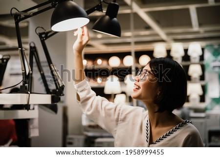 Asian young short hair beautiful woman wearing glasses choosing new lamp to buy at furnishings lighting store Royalty-Free Stock Photo #1958999455