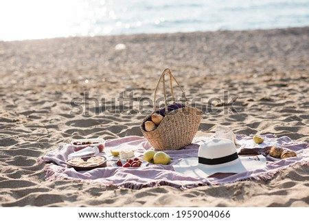 Having picnic with fresh bread, straw bag and hat on blanket at sandy beach over sea shore at background. Summer season. Vacation time.  Royalty-Free Stock Photo #1959004066