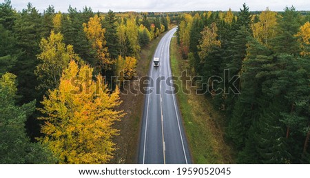 Truck on a autumn color road, aerial, drone shot, of a vehicle on a route, in middle of fall forest, dark, cloudy, fall day, in Scandinavia