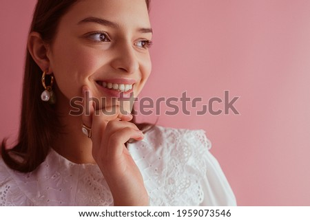 Happy smiling girl wearing trendy pearl earrings, vintage blouse with lace collar, posing on pink background. Close up portrait. Copy, empty space for text