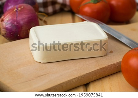 Block of Greek feta cheese on a wooden cutting board  close-up. There is a knife on the board next to it. There are tomatoes and onions on the table. Royalty-Free Stock Photo #1959075841